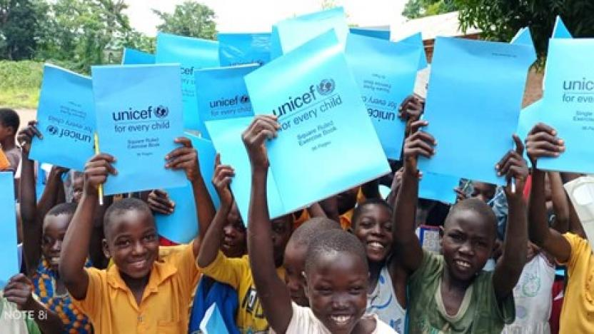 Children showing school supplies to the UNICEF delegation to confirm that they had received them