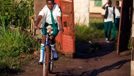 Windle Trust International - A student arrives riding a bicycle to attend the morning session at the ECSS Timbiro Secondary School in Yambio, Western Equatoria, South Sudan