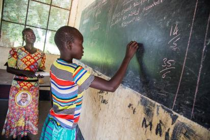 Girl pupil solves a maths problem with her female teacher in Rumbek